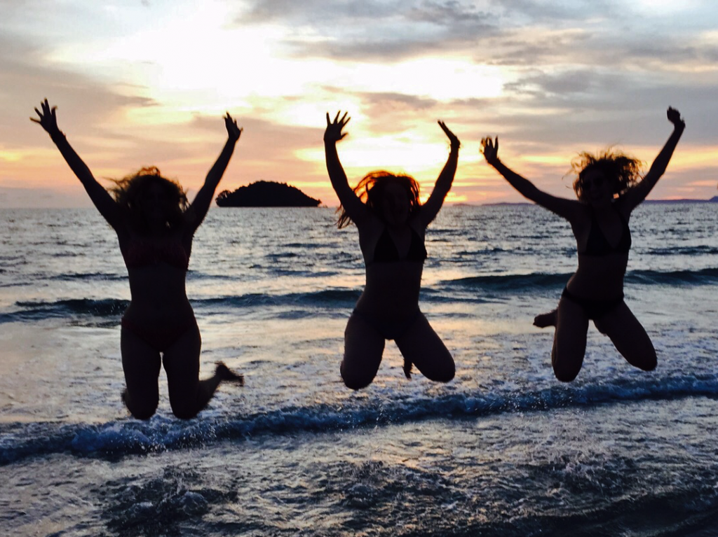 women leaping in the air on a beach