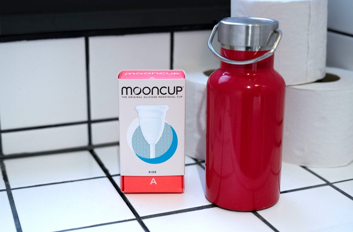 Mooncup in a public toilet next to a red reusable water bottle