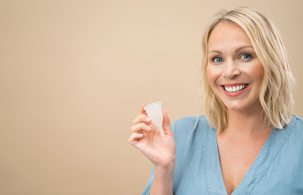 woman smiling and holding a mooncup menstrual cup